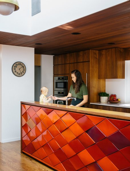 Aaron and Yuka Ruell transformed a 1950s Portland ranch house into a retro-inspired family home with plenty of spaces for their four children to roam. In the kitchen, interior designer Emily Knudsen Leland replaced purple laminate cabinets with flat-sawn eastern walnut, and added PentalQuartz countertops in polished Super White for contrast. The kitchen island is clad with original red tiles, and hanging cabinets above it were removed to maximize light and family-room views.