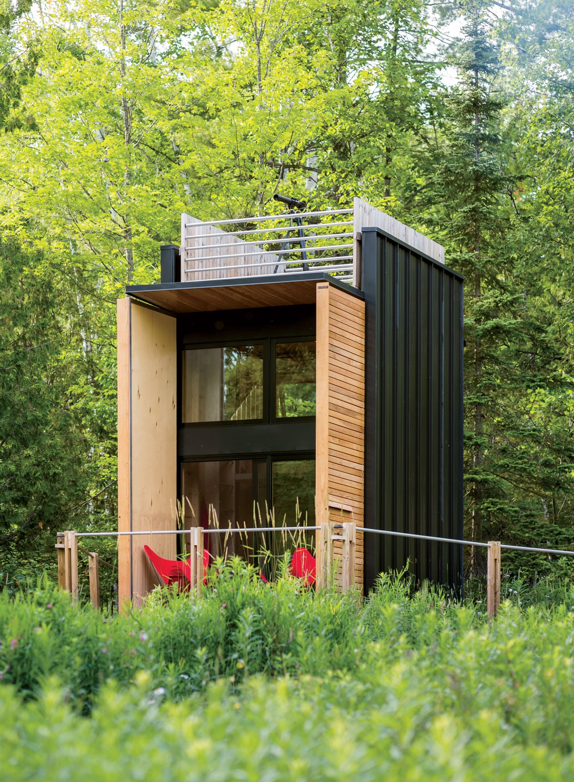 Exterior, Cabin Building Type, Flat RoofLine, House Building Type, Wood Siding Material, and Glass Siding Material Architect Bill Yudchitz asked his son, Daniel, to help him create a self-sustaining multi-level family cabin in Bayfield, Wisconsin.  Photo 56 of 101 in 101 Best Modern Cabins from Editor's Picks: 7 Inspiring Small Spaces