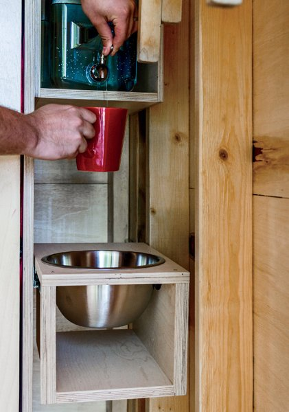 One corner holds a refillable water jug and a stainless-steel washbasin.