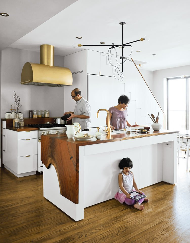 Kitchen, Wood Counter, Medium Hardwood Floor, White Cabinet, Range Hood, Range, Vessel Sink, Pendant Lighting, and Recessed Lighting The Mandayam–Vohra family's Brooklyn kitchen is highlighted by a gold hood that complements Workstead's signature three-arm chandelier, shown here in its horizontal configuration.  Kitchen from Ways to Use Gold Accents in the Kitchen