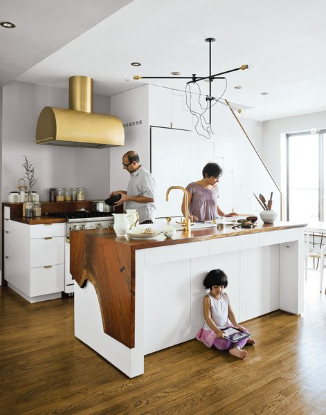 A couple takes a minimalist approach to their Brooklyn apartment, focusing on supple materials, subtle gradations of color, and custom finishes by local craftsmen. The Mandayam–Vohra family gathers under one of Workstead's signature three-arm chandeliers, shown here in its horizontal configuration. Bartenschlager designed the white cabinets and is responsible for the walnut counters both on the kitchen island and near the stove.