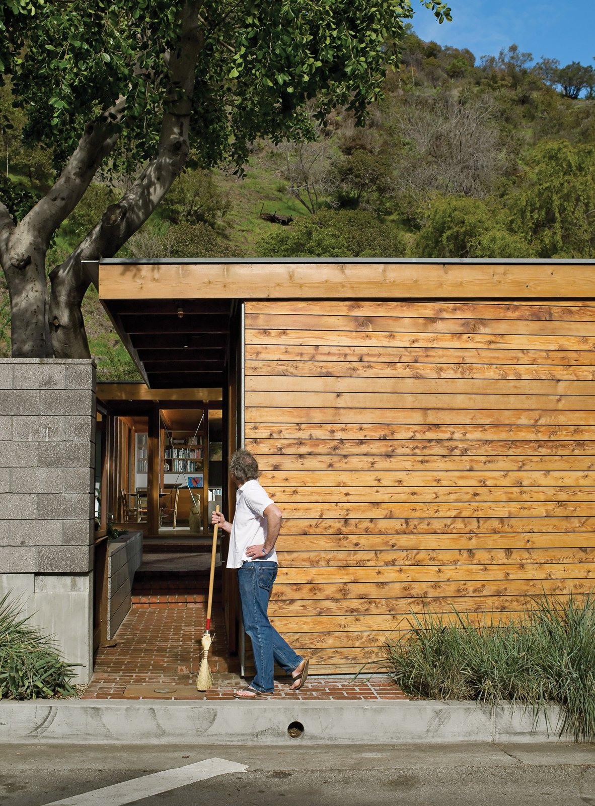 Outdoor and Small Patio, Porch, Deck Flanking the concrete wall is a carport and an entrance leading past a small, cedar-clad ancillary building for art projects and laundry.  Photo 7 of 12 in Compound Addition