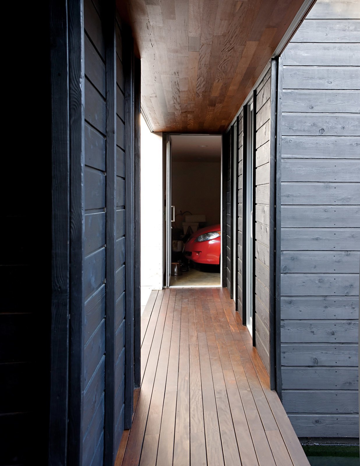 Hallway and Dark Hardwood Floor A perpendicular walkway leads right to the garage and laundry areas.  Nippon inspired from An Atypical Modern Home in Southern California