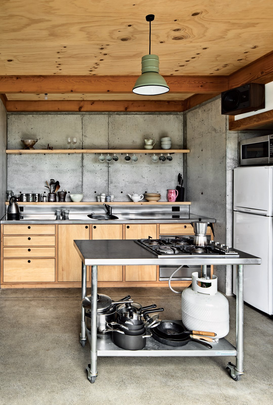 """Kitchen, Concrete Floor, Metal Counter, Pendant Lighting, and Concrete Backsplashe The designers fabricated everything in the house, down to the quarter-sawn pine and macrocarpa-wood kitchen cabinetry and concrete floor. """"Physically the most challenging part of the build was wrestling an incredibly slippery concrete pump up the muddy driveway in the rain!"""" says designer Ben Mitchell-Anyon. The enamel pendant light is vintage. Photo by: Paul McCredie  Ceilings"""
