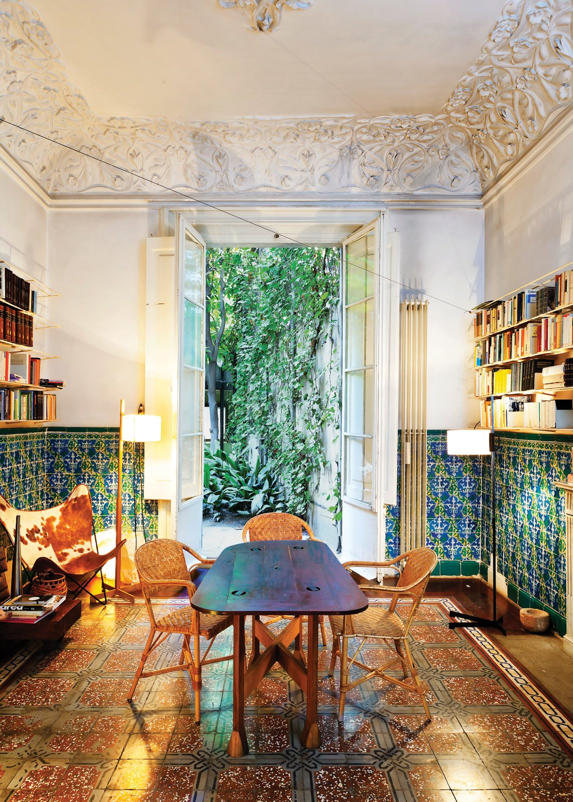 Dining Room, Chair, and Table In the dining room, which opens to the backyard terrace, original tilework on the floors and walls complement decidedly modern counterparts—an original 1938 Butterfly chair   by Antonio Bonet, Juan Kurchan, and Jorge Ferrari Hardoy, and a 1983 TMC floor lamp by Spanish designer Miguel Milá.  Photo 3 of 41 in 50 Dashing Dining Rooms