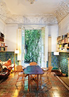 In the dining room, which opens to the backyard terrace, original tilework on the floors and walls complement decidedly modern counterparts—an original 1938 Butterfly chair   by Antonio Bonet, Juan Kurchan, and Jorge Ferrari Hardoy, and a 1983 TMC floor lamp by Spanish designer Miguel Milá.