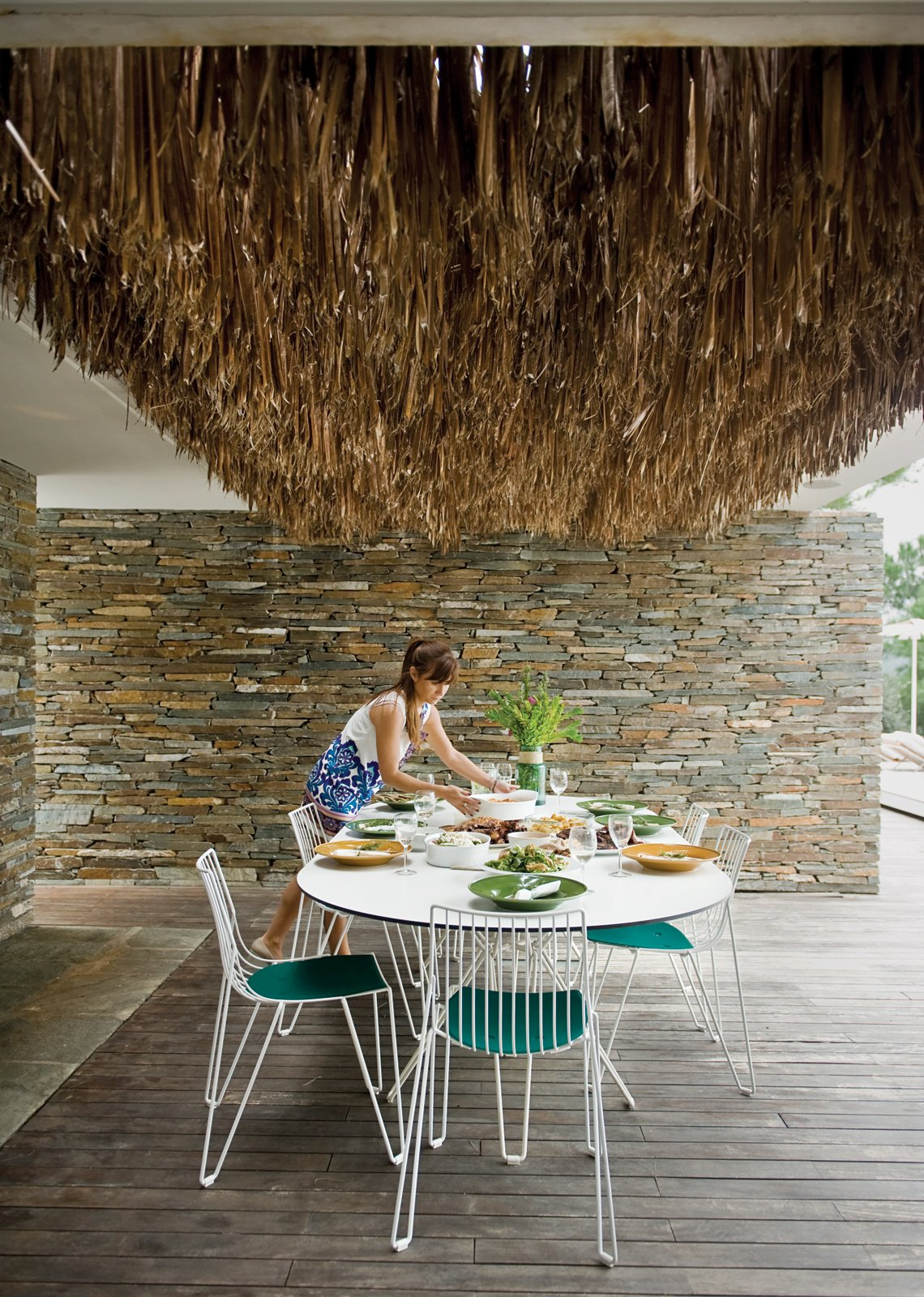 The Mourtzouchoses entertain constantly, which means that food is rarely far from anyone's mind. Alexia sets a Tio table (with matching chairs) by Massproductions, over which hangs a thatch of dried palm fronds.  Photo 41 of 41 in 50 Dashing Dining Rooms from An Idyllic Vacation Home in Greece