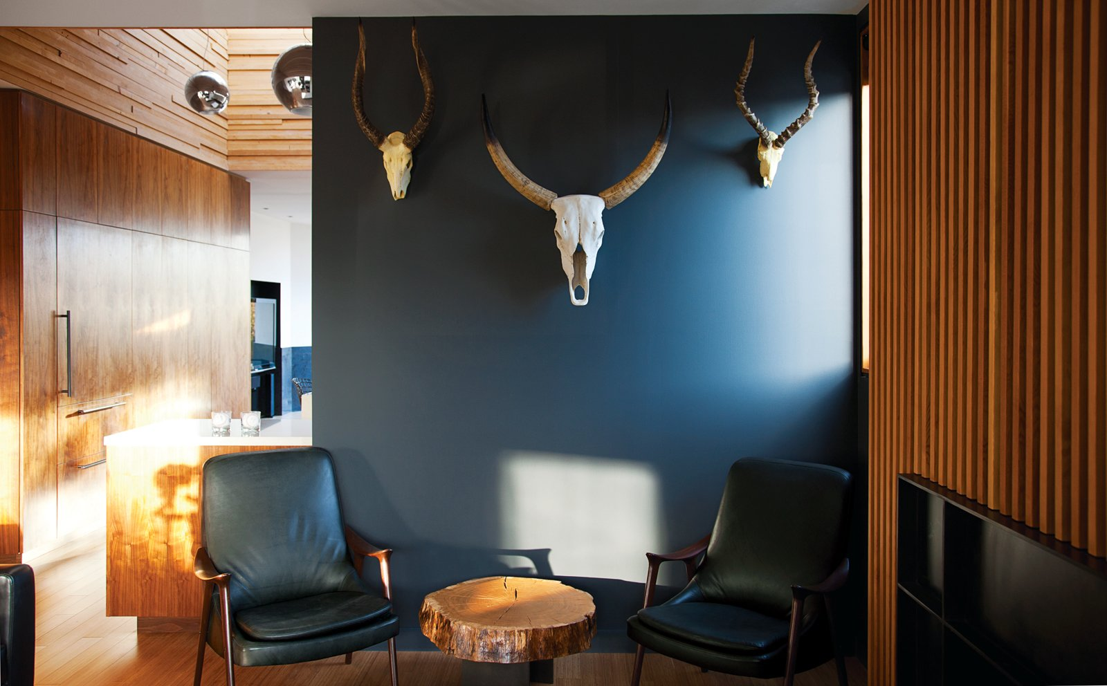 """Living Room, Chair, and Medium Hardwood Floor A trio of resin skulls works as manly wall art above a burly end table from Urban Hardwoods and on a wall painted with ICI Paint's Noble Grey.  Photo 7 of 9 in You Won't Be Calling This House a """"Man Cave"""""""