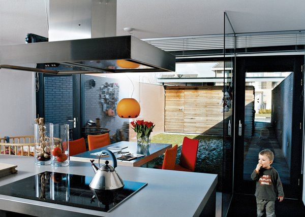 """The kitchen is the entrance point for the Collettes' home and its functional core. The warm colors of the house's wood-and-brick exterior are continued in the felt covers of the Face chairs in umber, red, and rust—a vintage 1983 design for Montis by Gerard van der Berg. The cupboards are gray (""""but a warm stone gray, not a cold corporate gray,""""Dedy emphasizes). Dark stone was planned for the countertop but looked far too heavy. The couple chose Duropal, a stainless steel lookalike that's easier to maintain."""