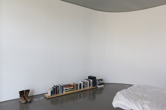 For a house in Phoenix, Arizona, Cy Keener's bedroom is on the far end the Spartan scale, but shows an interesting approach to balancing color. The gray floor and ceiling offset the white walls to add texture without adding clutter. The room contains a bed, a pair of boots, and a selection of books—and nothing else. Photo by Ye Rin Mok.  Photo 2 of 7 in Photographer Q&A: Ye Rin Mok