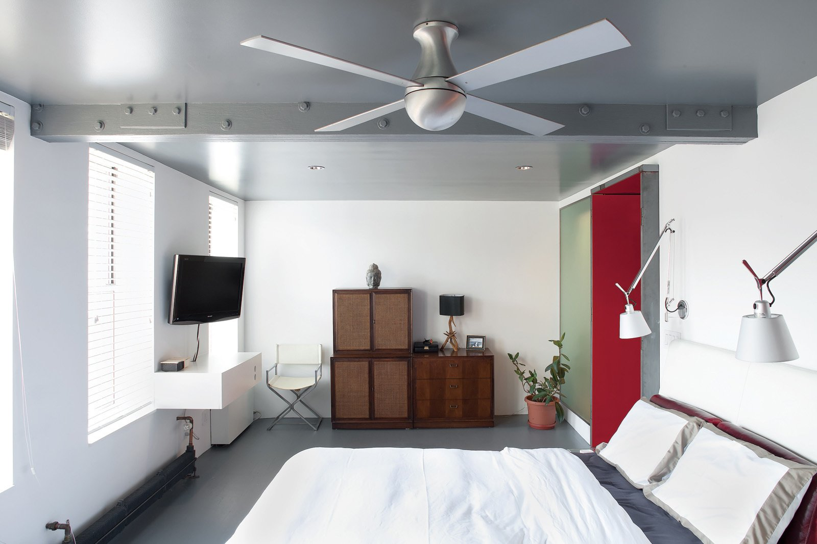 """Two-bedroom apartments are coveted in Manhattan, but the reality is that we are just two people, and the second bedroom had become neglected storage space,"" Fontanez says. Combining the two into one reaped big rewards. ""Now we wake up to a row of four windows and a variety of birds singing,"" Russell says.  Bedroom from Tunnel Vision"
