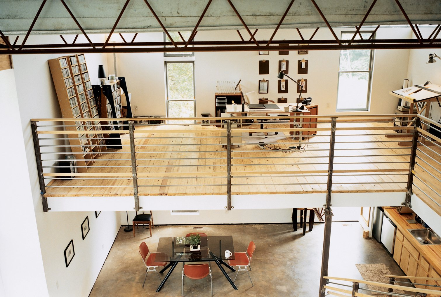 The bedroom overlooks an office, which floats above the kitchen and dining room. The railing and banister were fabricated by a local metal worker a few miles away.  Photo 3 of 8 in Mid-City Modern