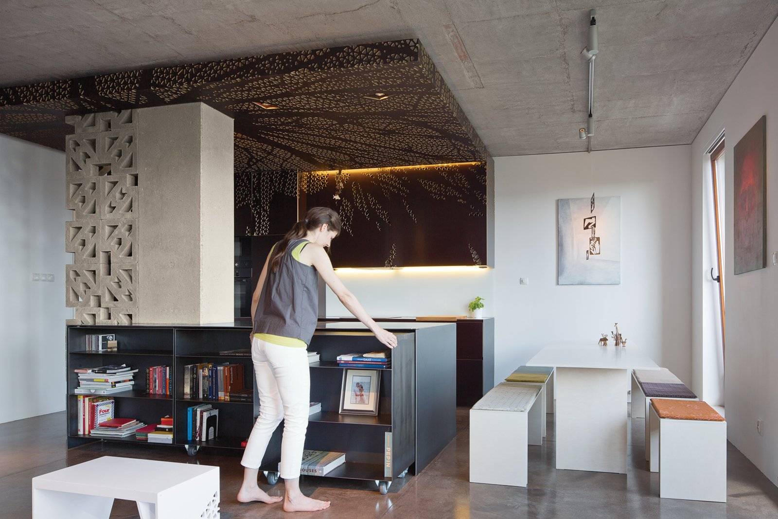 "Dining Room, Table, Bench, and Track Lighting A movable feast: In designers Nix and Novak-Zemplinski's 1,000-square-foot apartment's open-plan kitchen, dining, and living space, almost everything is convertible. Cookbooks are kept in low ""nesting"" shelving, keeping the countertops free.  Photo by Andreas Meichsner.  Stocking Stuffer Homes: Small, Mighty, and Under 1,000 Square Feet by Kelsey Keith from Warsaw Loft with Multifunctional Furniture"