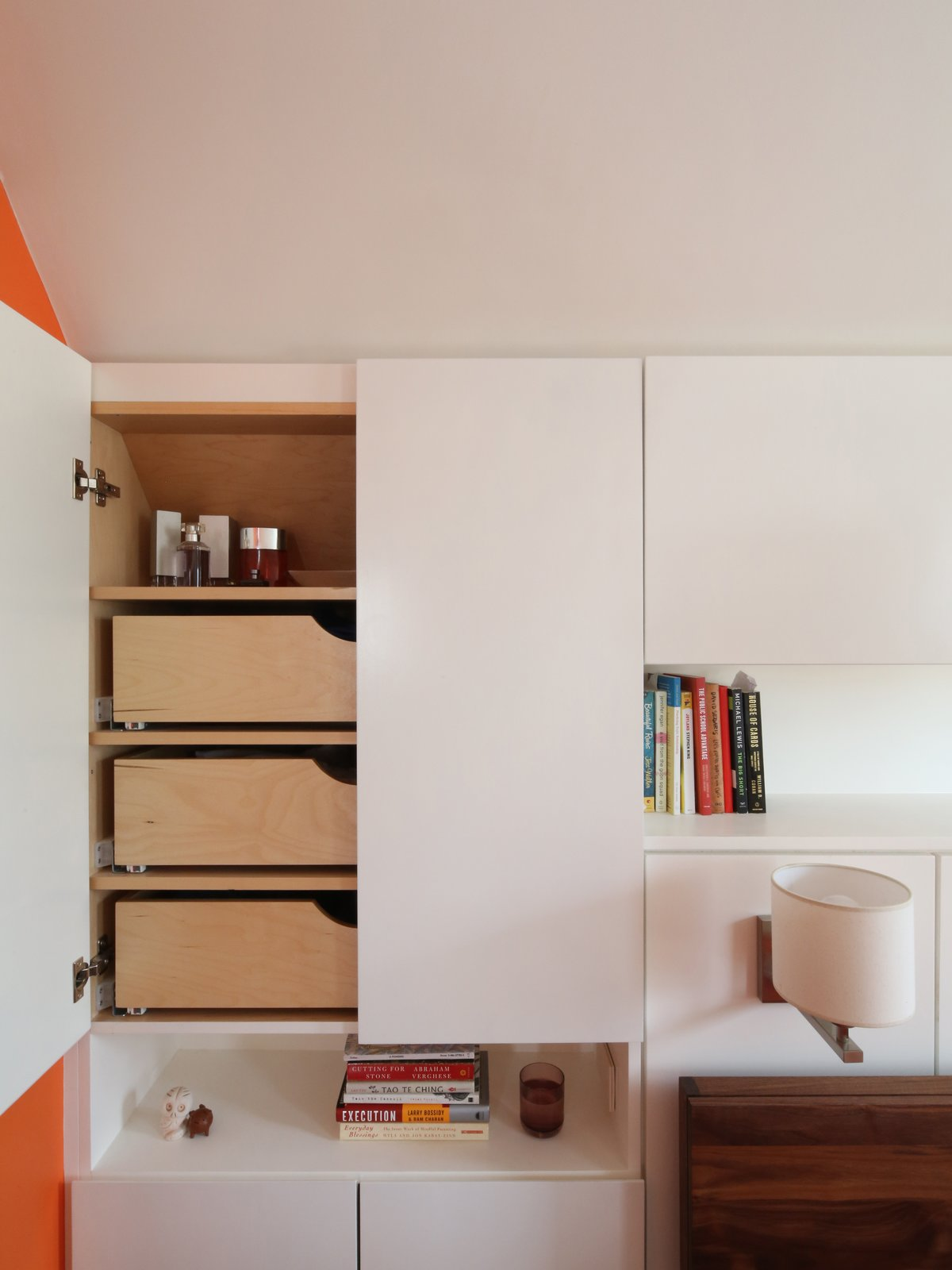 """In order to save space, Barrett designed custom storage under the shortest part of the sloped roof. """"The custom millwork was a big ticket item, but critical to making the suite feel spacious,"""" Barrett says. """"Built- in storage is good value for the money because it allows you to harvest previously unusable space and it allows a smaller space to feel larger since you don't need a lot of furniture.  How To: Bright Bedroom Renovation  by Olivia Martin"""