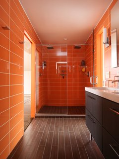 In the bathroom, Roca wall tile in Rainbow Azul continues the citrus color scheme, and the floor is clad in ceramic plank. The Ikea sinks and faucets also helped the design come in on budget.