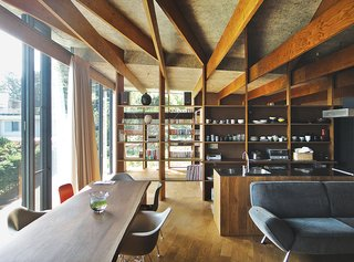 In the open living and dining room of a hillside family home in Japan, Eames shell chairs surround a custom walnut table by Kagura. The upholstered seating is by Arflex. The architect, Masahiro Harada of Mount Fuji Architects Studio, also designed the custom kitchen island and stove vent.