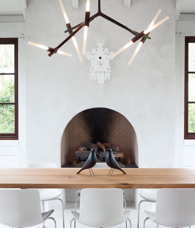 The home's informal dining space has a slightly rustic feel, sporting bronze and wood in the form of a Lindsey Adams Adelman chandelier for Roll & Hill and a table by Terry Dwan, mixed with folk-art touches like the Eames House Birds and a cuckoo clock from Diamantini & Domeniconi. Photo by Gregory Miller  Photo 5 of 6 in Design Classic: Eames House Bird