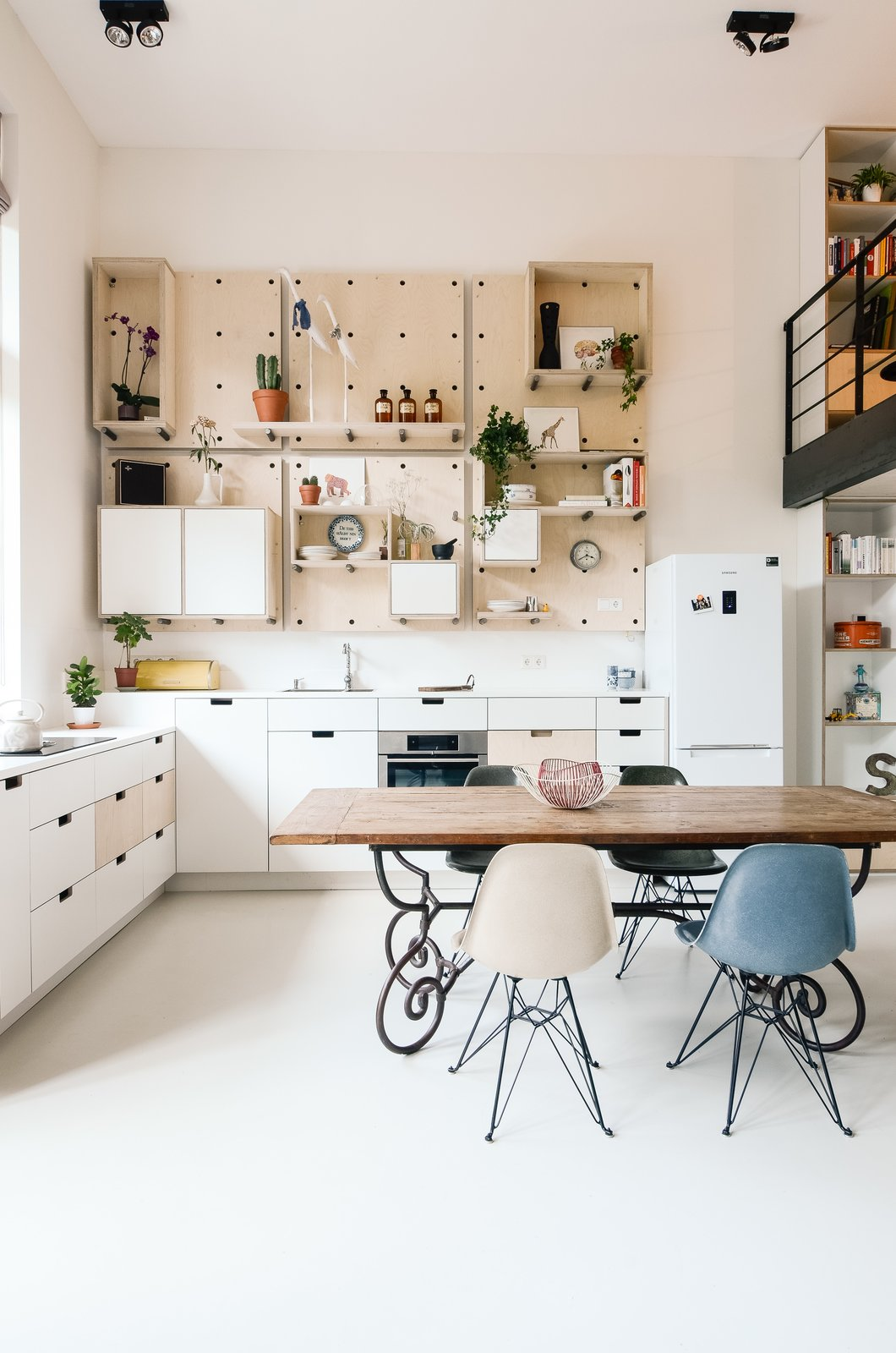Kitchen, Refrigerator, White Cabinet, Open Cabinet, and Ceiling Lighting The kitchen is completely open to the main living area and features a custom birch pegboard wall. Eames dining chairs accent the space.  Photo 4 of 21 in 20 Dream Kitchens from Schoolhouses Turned into Modern Homes