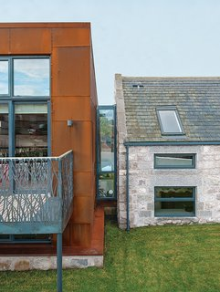 "Cor-Ten steel from a ship building yard clads the new structure, which connects via a glass ""bridge"" to a rebuilt stone farmhouse containing the bedrooms."
