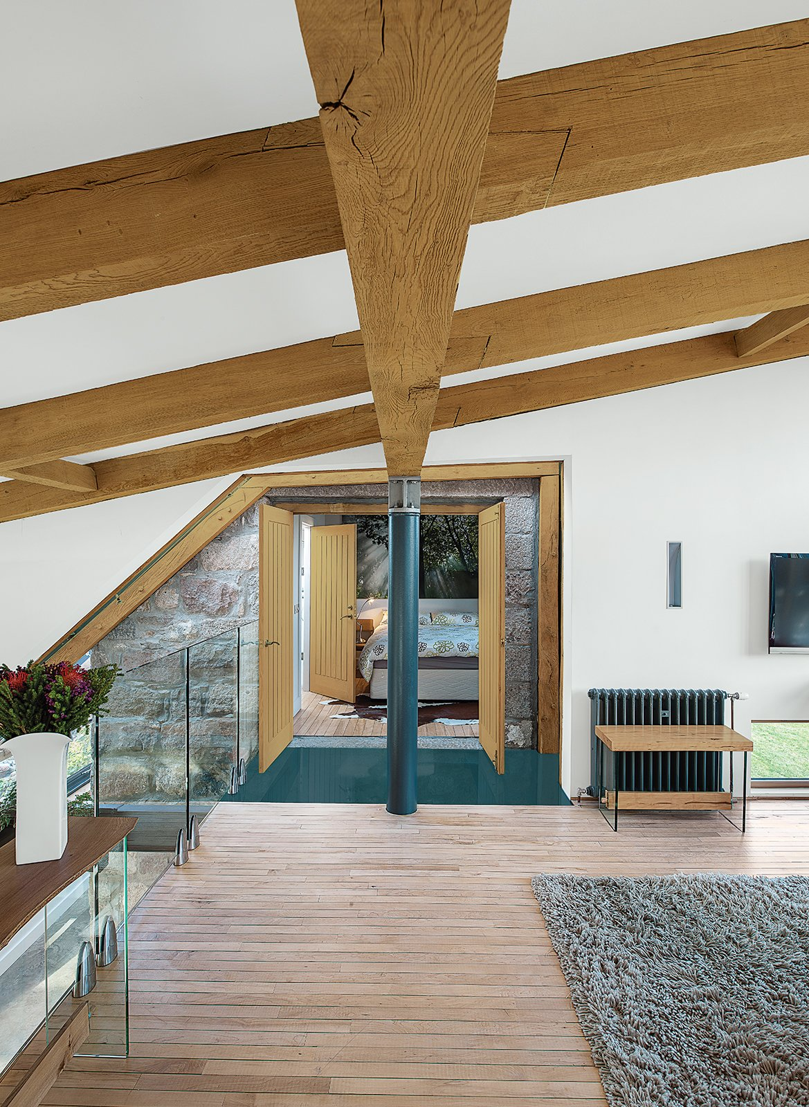 Living Room and Light Hardwood Floor Reclaimed oak beams dominate the upstairs lounge, which leads to the guest bedroom.  40+ Homes With Exposed Beams: Rustic to Modern by Luke Hopping from This Farmhouse is a Cor-Ten Steel-Clad Dream