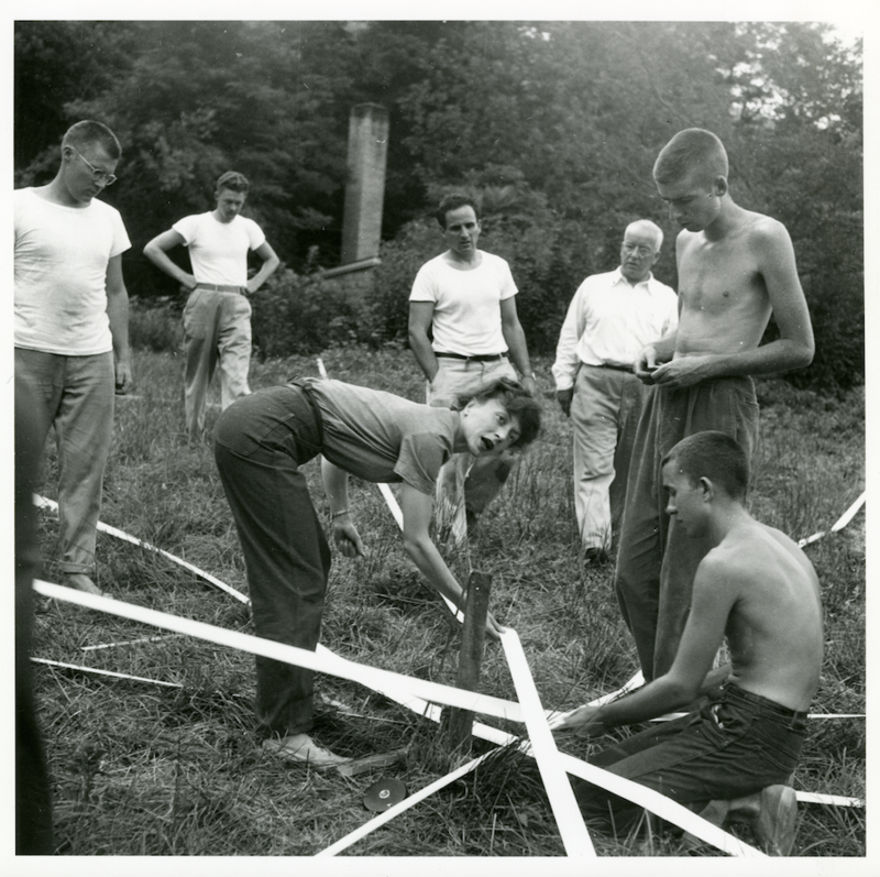 Elaine de Kooning (center) and students Ray Johnson (right foreground) and Albert Lanier (far right foregound) work on Buckminster Fuller's Supine Dome, as Fuller (background, in glasses) looks on.