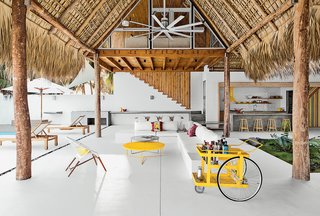 The living-dining area of a beach house designed by El Salvador firm Cincopatasalgato features a custom bar cart by local designers Claudia & Harry Washington, a built-in sofa, and an Ikono chair and Circa low tables by The Carrot Concept. An Isis model from Big Ass Fans is above.
