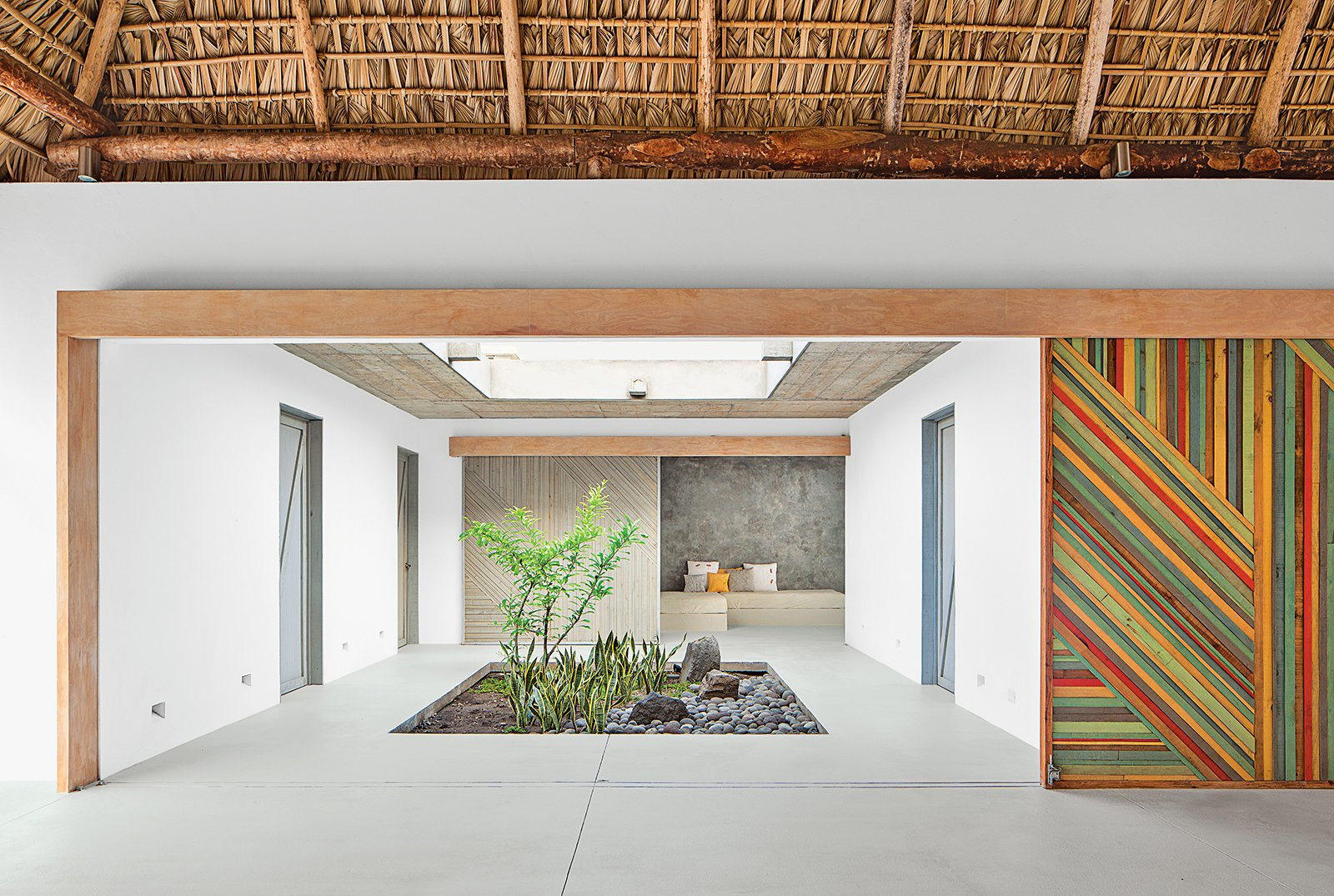 "Architect José Roberto Paredes calls the sliding walls utilitarian artwork. ""The doors open to a surprise space, like a secret pathway,"" he says.  Impressive Indoor Gardens by Allie Weiss from An El Salvador Beach House with an Interior Courtyard"
