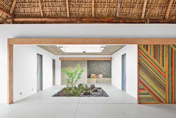 """Architect José Roberto Paredes calls the sliding walls utilitarian artwork. """"The doors open to a surprise space, like a secret pathway,"""" he says.  Creative Ways to Bring Light Into the Home by Heather Corcoran from An El Salvador Beach House with an Interior Courtyard"""