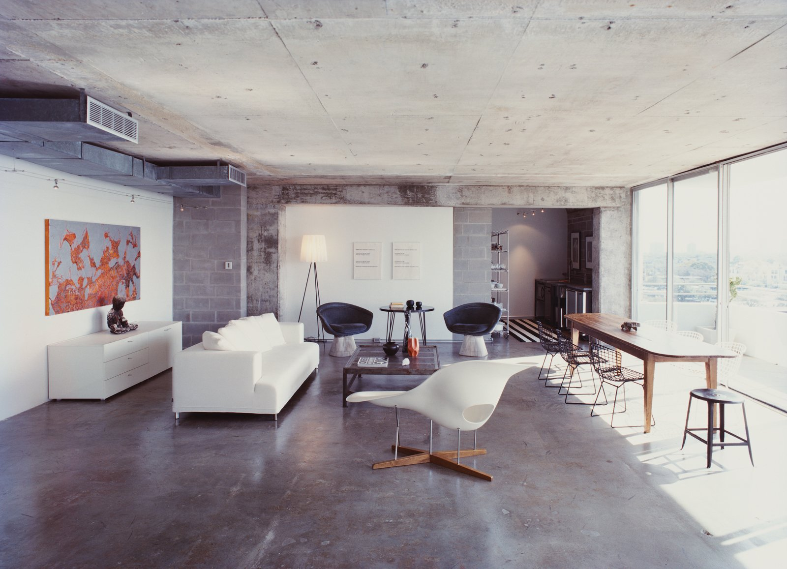 Living Room, Chair, Sofa, Coffee Tables, Floor Lighting, and Concrete Floor A Philippe Starck standing lamp and an Eames chaise longue bracket the living room; two Lawrence Weiner prints hang behind a pair of Warren Platner chairs and a table purchased from a River Oaks estate sale; at far left of the room, a partial wall of new cinderblocks hides a return air vent.  Photo 3 of 11 in Stripped Ease