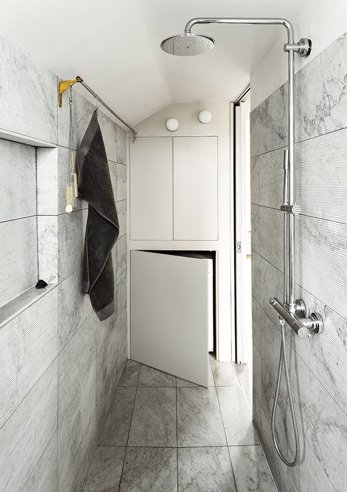 Bath Room, Full Shower, Enclosed Shower, Wall Lighting, Marble Wall, and Marble Floor The Salvatori marble tiles in the bathroom were added at the last minute, once everyone was confident that they would not put the project over budget.  Photos from This Is How You Can Live Large in a Small Space