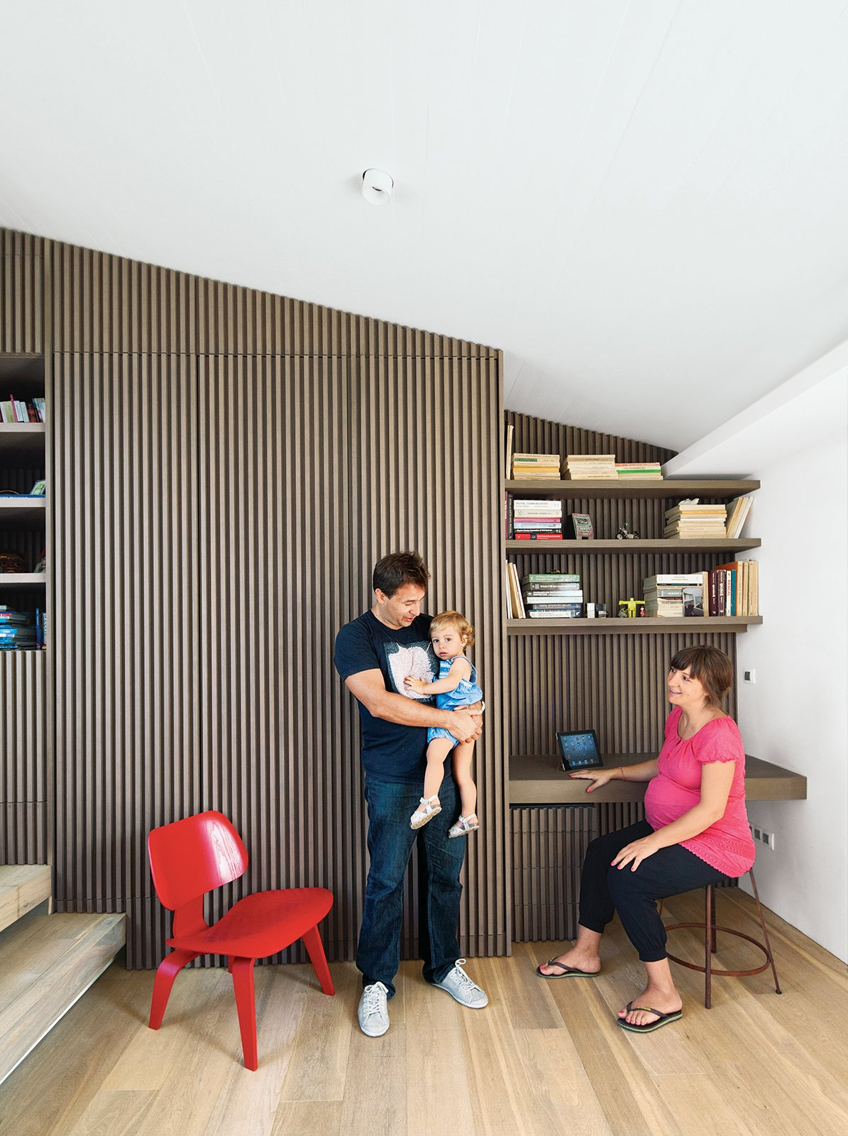Office, Chair, Desk, Shelves, and Light Hardwood Floor Iason Vassiliou, Maria Voutsina, and their daughter, Angeliki, relax in a landing-level office at their apartment in Athens, Greece.  Ideal Angles by Jill Southern from Odd Angles Don't Stop This Apartment's Transformation