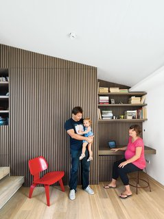 Iason Vassiliou, Maria Voutsina, and their daughter, Angeliki, relax in a landing-level office at their apartment in Athens, Greece.