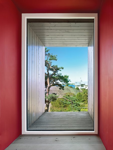 """""""The color Falu-red, or Falu Rödfärg, is used for houses all over Sweden,"""" says Pineus. """"It's such a strong color, but I think it works."""" Each of the house's protruding boxes feature pine slats painted in a silver tar, which contrasts the larch of the interior and offers a sturdy defense to the ocean air."""