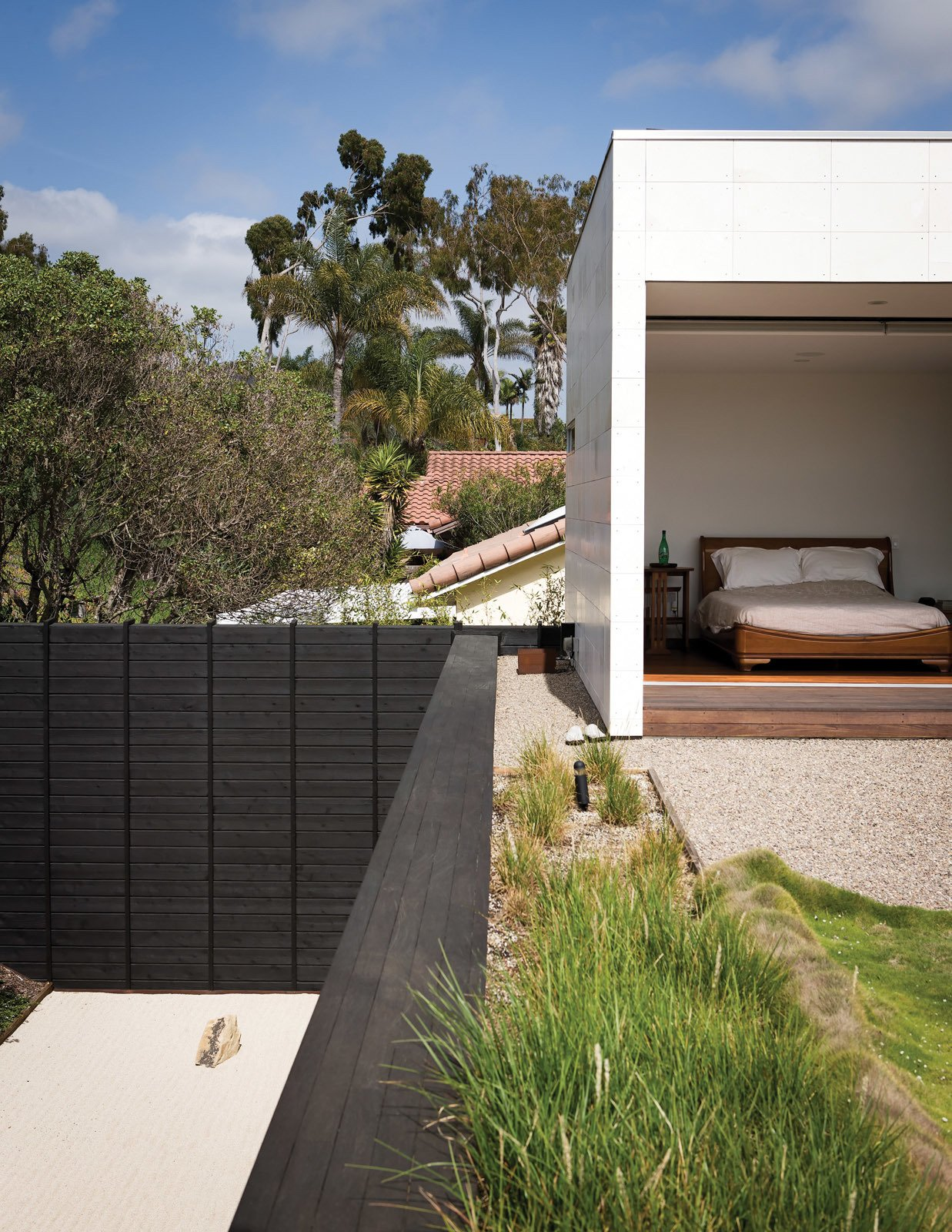Bedroom and Bed The limestone-clad volume at the east end of the house extends to the second story, housing Shino and Ken's master suite, which opens onto the planted roof deck.  Limestone Designs in Modern Homes by Zachary Edelson from An Atypical Modern Home in Southern California