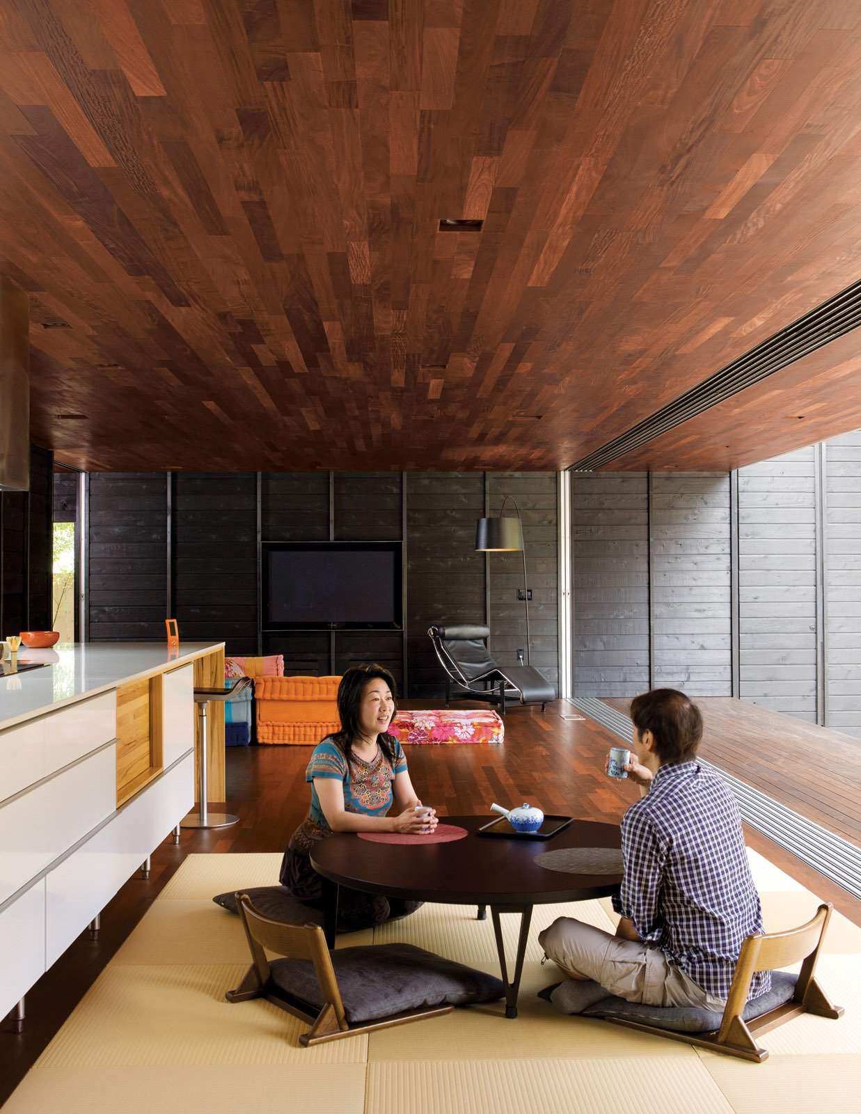 Living, Coffee Tables, Chair, and Dark Hardwood At the client's request the kitchen contains neither upper cabinets (Shino can't reach them) nor an oven (they only used the old one once—to reheat a pizza). A modular Roche Bobois Mah Jong sofa adds a decorative flourish to the living area while maintaining as low a profile as the traditional Japanese furniture.  Best Living Chair Dark Hardwood Photos from An Atypical Modern Home in Southern California