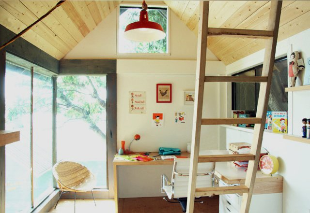 Reclaimed materials like salvaged windows and doors kept costs down, while white paint, bright customized workspaces, and custom millwork keeps things airy on the interiors.  Photo 1 of 3 in Tiny Studio Cabin by Hinterland Design