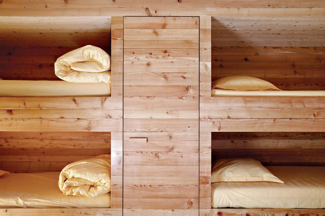 The entire Wooden Cabin—including the sleeping cubbies, shown here—is clad in locally sourced larch, which over time will turn gray then black. Read the full story here.  Photo 5 of 9 in First-Class Cabins