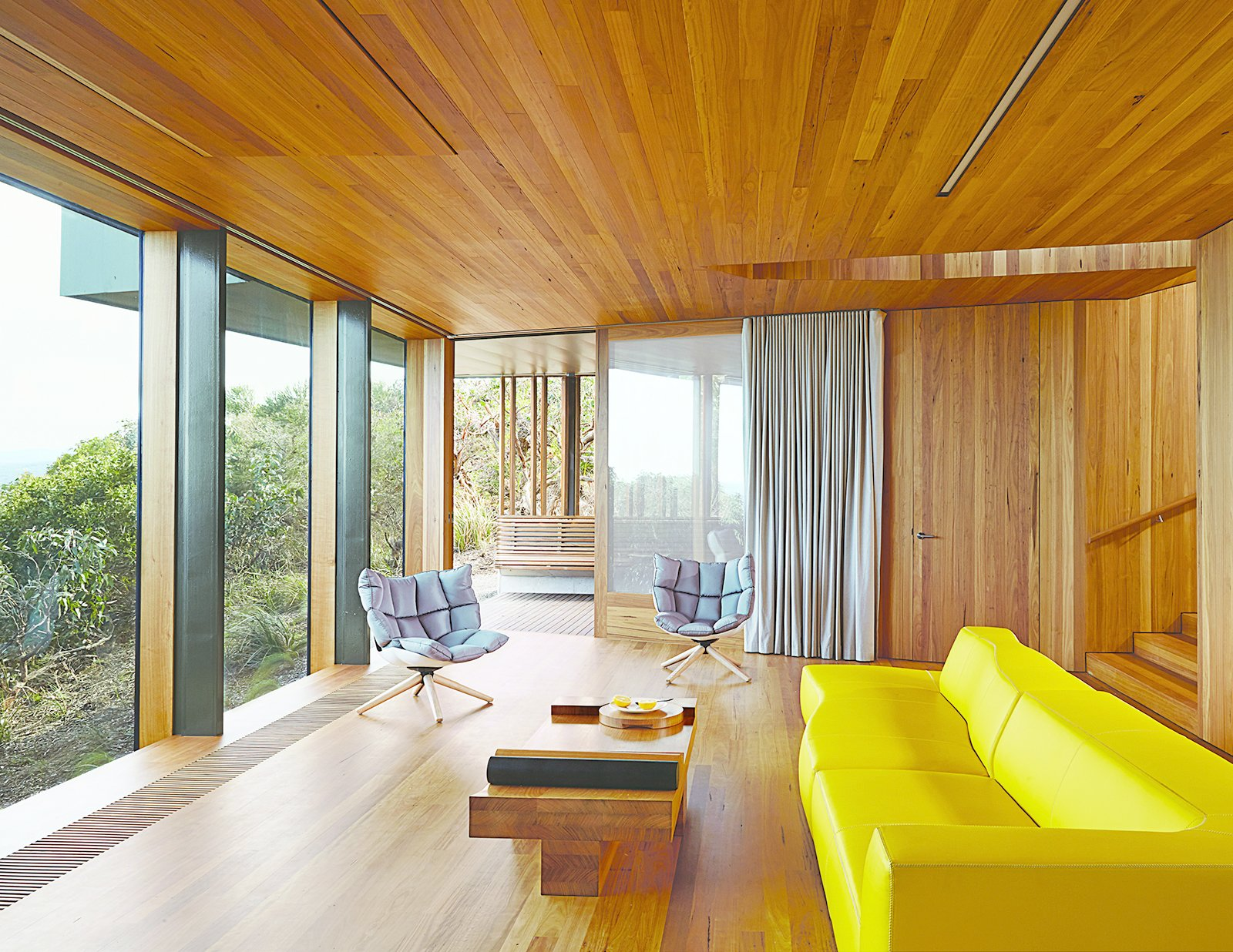 Refusing to fixate on the seascape at the expense of other views, Wardle oriented the living room to a lush grove of trees. A yellow Bend sofa and two Husk chairs, both by Patricia Urquiola for B&B Italia, add splashes of color.  Instances of Patricia Urquiola-Designed Pieces in Modern Homes by Zachary Edelson