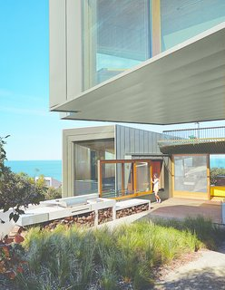 """A sliding window between the kitchen and the barbecue area makes outdoor cooking a cinch. """"In summer, we eat out there a fair amount,"""" the wife says. Wardle chose zinc for the exterior to complement the trees that surround the house on its northern fringes."""