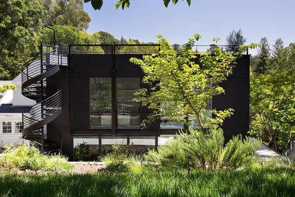 """The decidedly industrial exterior features smooth dark gray stucco, a custom steel mesh wall, and a metal spiral staircase leading from the ground floor to the roof deck. The clients love the industrial look because it feels raw and natural to them. The footprint of the new addition lies at the rear of the existing home, and the dark exterior helps seamlessly integrate the new structure into the natural slope of the land. According to architect John Klopf, the new addition acts as a spatial backdrop for the existing structure, """"receding visually out of respect for the original home."""""""