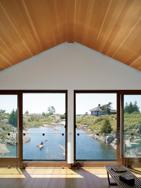 Sometimes the best way to deal with a tall, gabled ceiling is to just add windows. A line of windows in the Floating House in Lake Huron, Ontario provides a picturesque water view.  Photo by Raimund Koch.