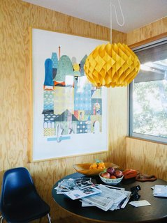 Natural wooden walls clad the dining room corner, while a marigold lantern hangs above.