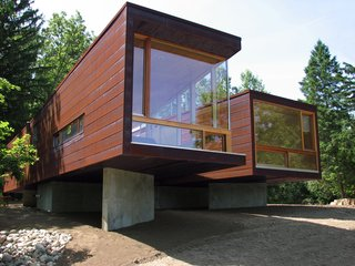 "Architect Jim Garrison of Brooklyn-based Garrison Architects was asked to design a retreat for visiting families on an idyllic lakeside expanse of land at a boarding school for troubled teens, Star Commonwealth in Albion, Michigan. To drastically reduce academic interruption and cut site noise, Garrison decided early on to create an 1,100-square-foot modular building dubbed Koby, with two bedrooms on opposite sides of the structure and a common dining area in the middle ""as a therapeutic space for families to gather and eat together."""
