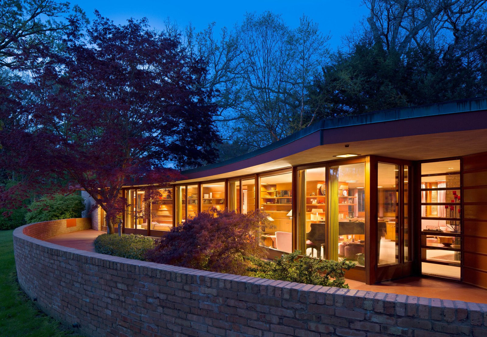 Outdoor, Stone Fences, Wall, Large Patio, Porch, Deck, Shrubs, Trees, and Side Yard The Kenneth and Phyllis Laurent House, designed by Frank Lloyd Wright, features a solar hemicycle footprint. Image courtesy of Wright Auction House.  Photo 4 of 10 in 10 Modern Iconic Masterpieces from Accessible Frank Lloyd Wright House in Illinois Is Reborn as a Museum