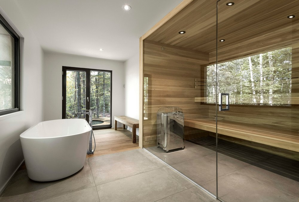 Bath Room, Freestanding Tub, and Concrete Floor A sauna is an optional feature. Cedar and concrete create a recurring visual theme from the exterior to the interior.  Spahaus by Allie Weiss from Saunas in Modern Homes