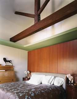 The Suarezes opted for a cozy bedroom with beautiful details, old and new—lustrous mahogany behind the bed, Baker tables beside it. The long beam overhead replaced the original, but smaller beams above it are authentic.