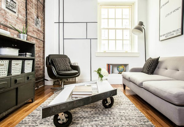 The New Project Group renovated a cramped, uninviting space on Manhattan's Upper East Side. The company gave the 400-square-foot apartment a gut renovation, with a new kitchen and bathroom designed for efficiency. A parallelogram-shaped window pane, rescued from an architectural salvage yard, was outfitted with steel edges and casters, and repurposed as a coffee table.