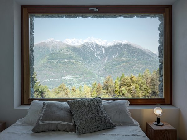 Views of the Orobie Alps can be seen from the home's windows, which also feature larch frames. A lampadina light by Flos sits on the nightstand.