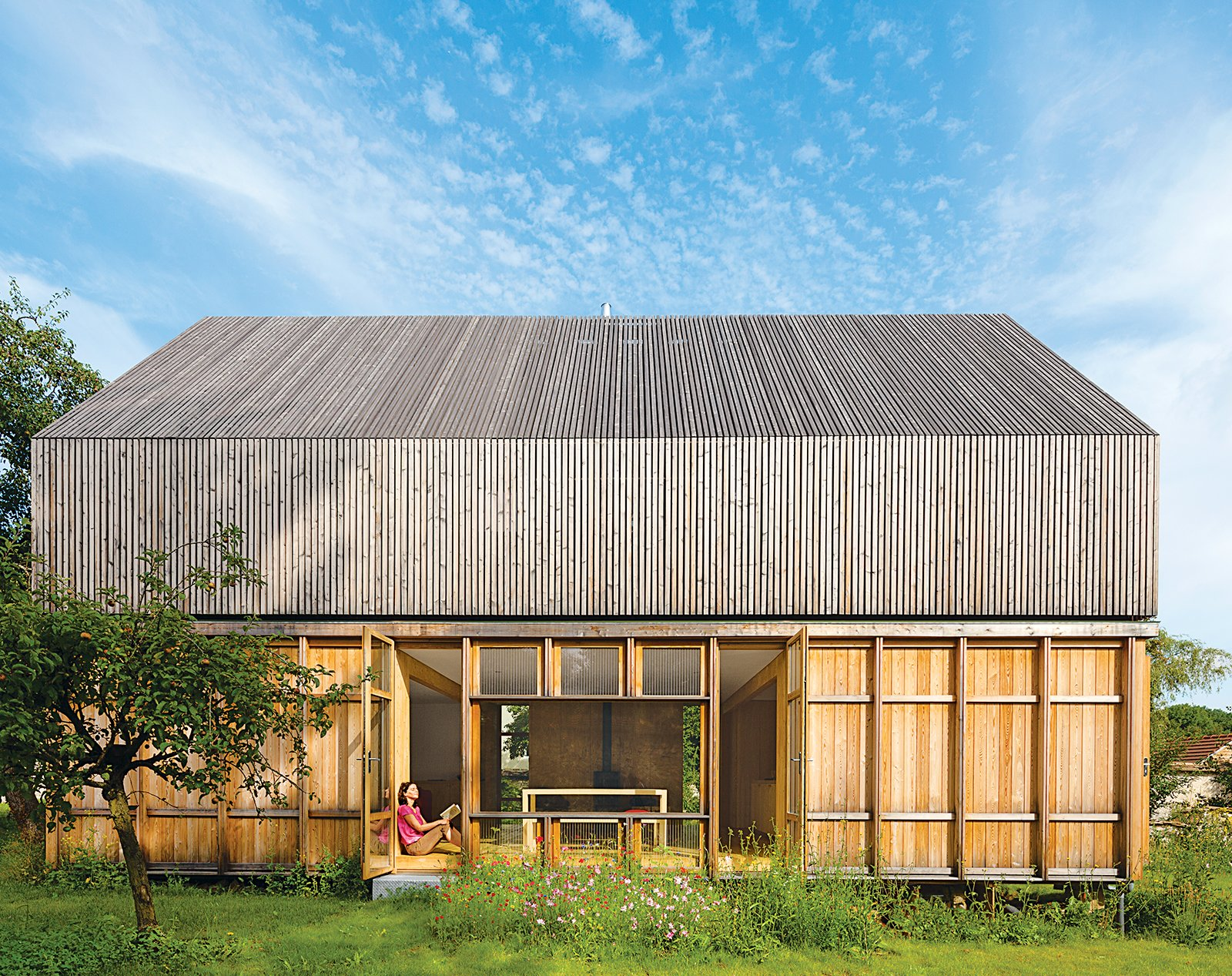 """Back Yard, Exterior, Wood Siding Material, and House Building Type The house has four varieties of wood that relate to one another with a similar material vocabulary. """"It is all about finding ways to assemble pieces of the same nature,"""" says Lamine.  Photo 2 of 4 in Eco-Friendly A-Frame in the French Countryside"""