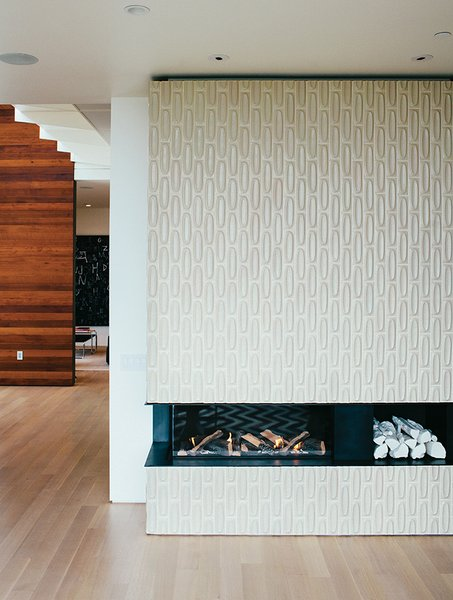 Architect George Bradley and his husband, Eddie Baba, renovated a 1941 house in San Francisco. Tiles from Heath Ceramics surround the Ortal Clear 130LS fireplace. The white ceramic logs are by Klein Reid; the floor is oak.